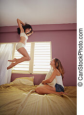 yound adult women jumping for joy on bed - two caucasian...