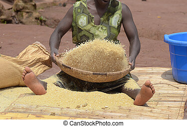 African woman sifts corn