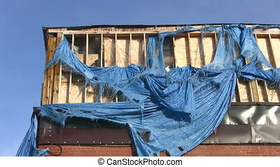 Bad tarp job. - A blue, ripped tarpaulin flaps in the wind.