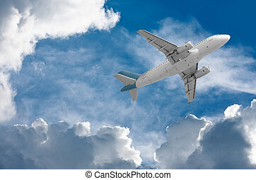 airplane travel - airplane flying through clouds towards the...