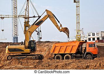 Backhoe loading a dump truck - A backhoe loads the soil in...