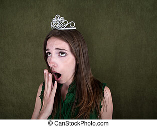 Bored Homecoming Queen - Young woman with crown on green...