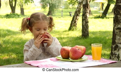 little girl eat apple in park