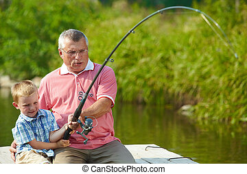 Fishing together - Photo of grandfather and grandson pulling...