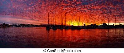 Crimson sunset over sailboits in marina