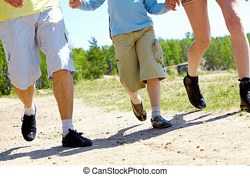 Go hiking - Legs of three family members going down forest...