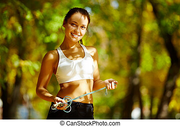 Cheerful sportswoman - A young woman holding a skipping...