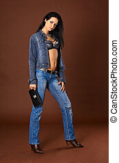 Young woman in fashionable jeans with a handbag on a brown...