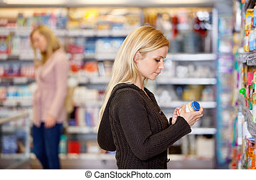Young Woman Product Compare - Young woman comparing products...