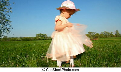 happy little girl in dress on meadow
