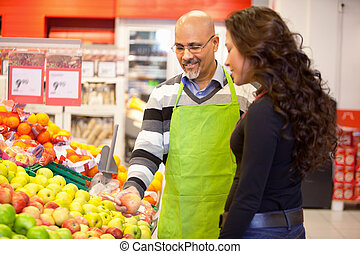 Woman Buying Groceries - A woman buying groceries receiving...