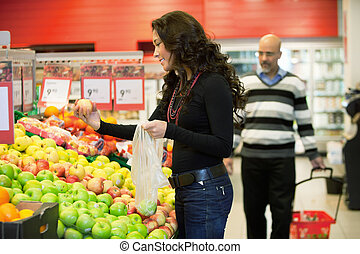 Woman Buying Fruit - Young woman buying fruits in the...