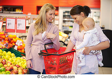 Mother carrying child with friend while shopping in...
