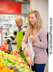 Young woman buying fruits with shop assistant in the...