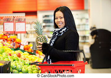 Asian Woman Buying Fruit - Portrait of a cheerful young...