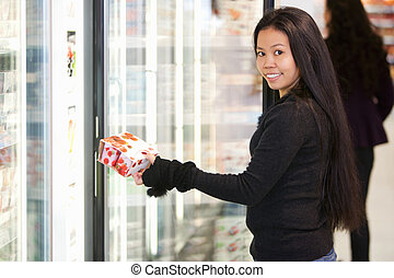 Woman Buying Yogurt - Portrait of a young woman holding box...