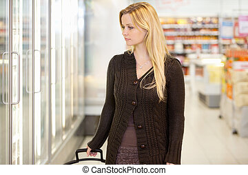 Supermarket Shopping Woman - Young woman looking at goods in...