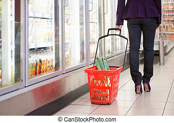 Woman with Shopping Basket - Low section of woman walking...