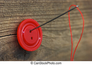 Buttons with needle and thread on the board