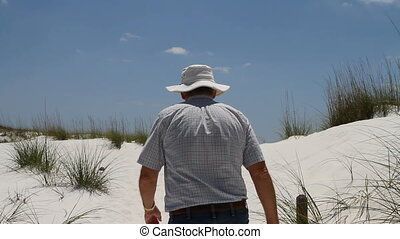 Man Walking Up Dune - Mature man wearing a hat walks up a...