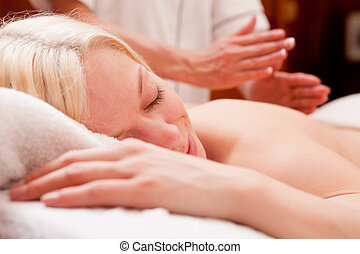Woman Receiving Percussive Massage - A relaxed blond woman...