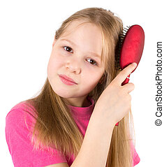 The beautiful girl brushes hair with a hairbrush