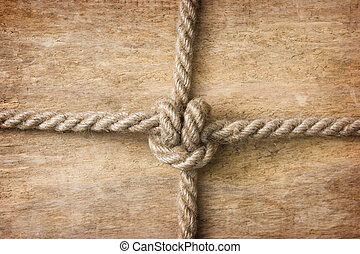 Rope with knots on the background of the old wooden boards