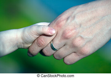 FIRST STEPS - Image shows a hand of an adult holding the...