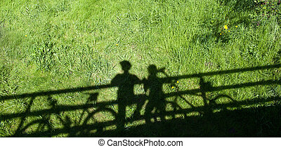two mountain bikers' silhouettes during a halt on a bridge