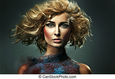 Young blonde beauty and flecks of colored sand