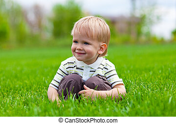 Smiling little boy sitting in fresh grass Shallow DOF effect...