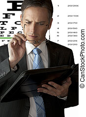 Businessman Puts On Glasses To Read