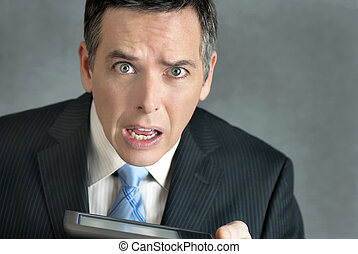 Businessman Confused By Tablet - A close-up shot of a...