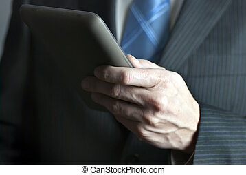Businessman Holds Tablet Computer - A close-up shot of a...