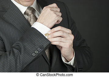 The Cufflink 2 - A - Close-up of a businesman adjusting his...