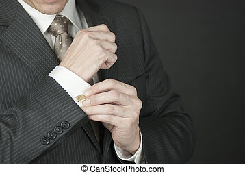 The Cufflink - A - Close-up of a businesman adjusting his...
