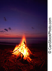 Beach Campfire - Blazing campfire at sunset along the...