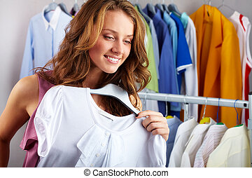 In clothing department - A girl choosing a t-shirt in the...