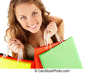 Happy shopper - Close-up of a girl with paper bags looking...