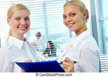 Two employees - Photo of pretty females looking at camera...