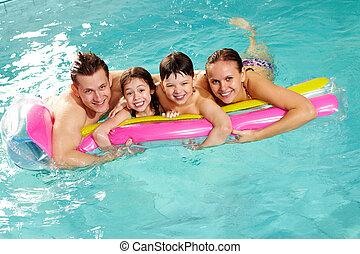 Good rest - Cheerful family in swimming pool having nice...