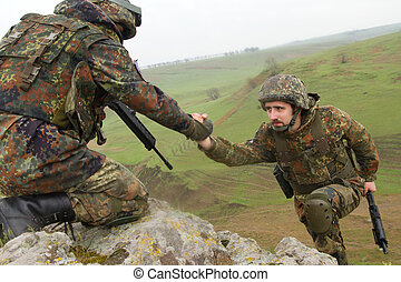 Soldier gives hand to his partner - Military man helping his...