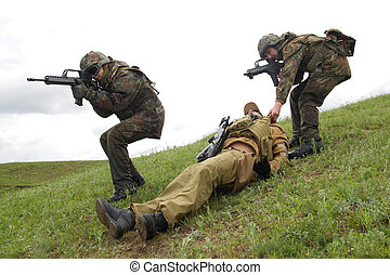Soldiers saving their wounded partner - Military men...