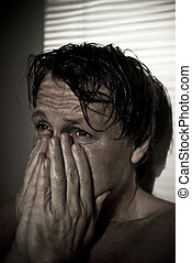 An extremely distressed man crying.