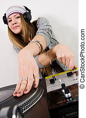 Female DJ scratching the record - Young attractive teenage...