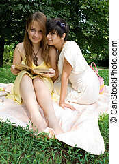 Two young girls sitting on coverlet upon green grass