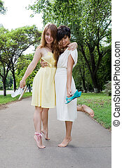 Young girls walking barefoot in the park - Copule of late...
