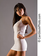Studio fashion - Beautiful Asian woman in slinky dress on...