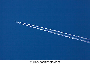 Aircraft and contrails - An airplane with a white vapor...