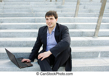Modern business man outdoors sitting on the stairs of the...